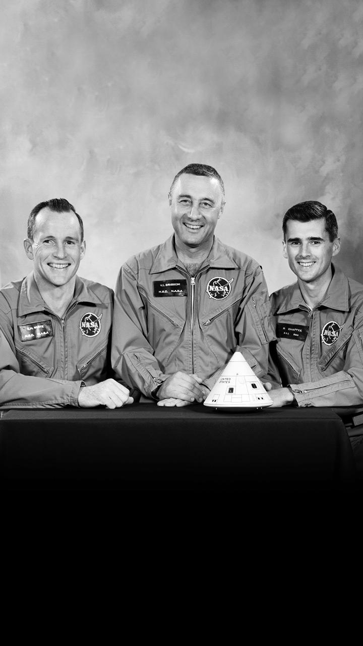 Three men smile at the camera.