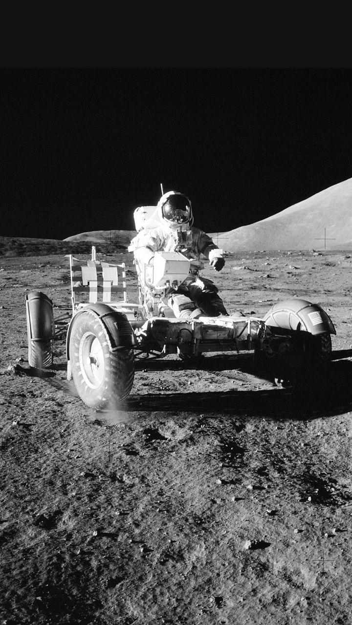 An astronaut in a space suit on a cart on the moon.