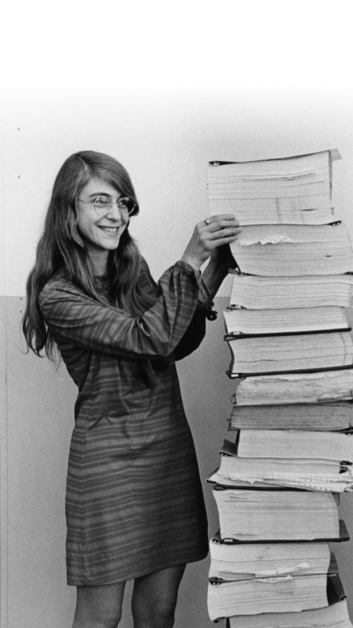 A woman stands next to a stack of books as tall as she is.