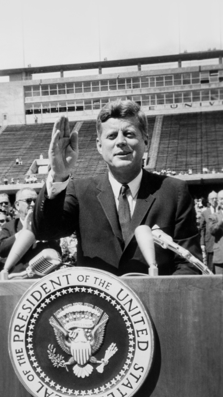 President Kennedy smiles and waves while standing in a stadium.