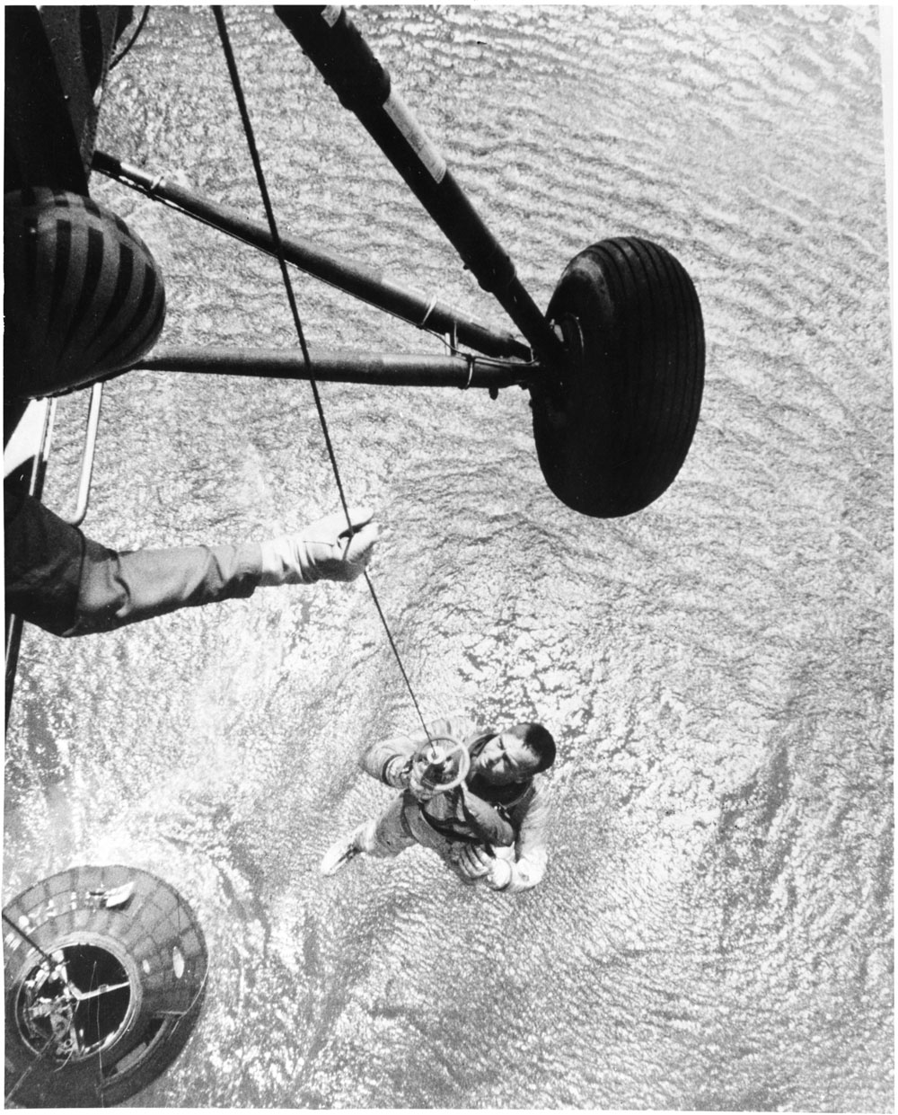 A Navy helicopter hoists Alan Shepard from the ocean after his flight.