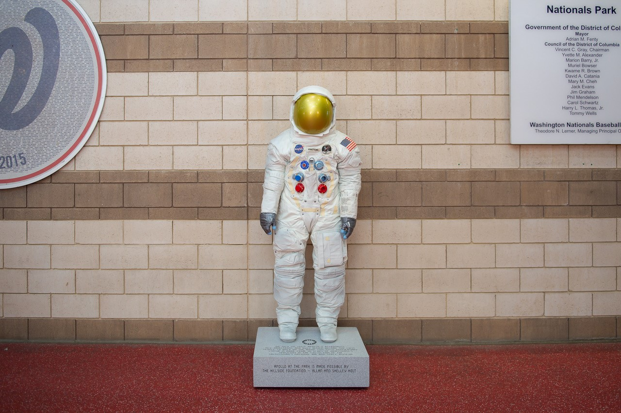 Spacesuit statue against light brick wall