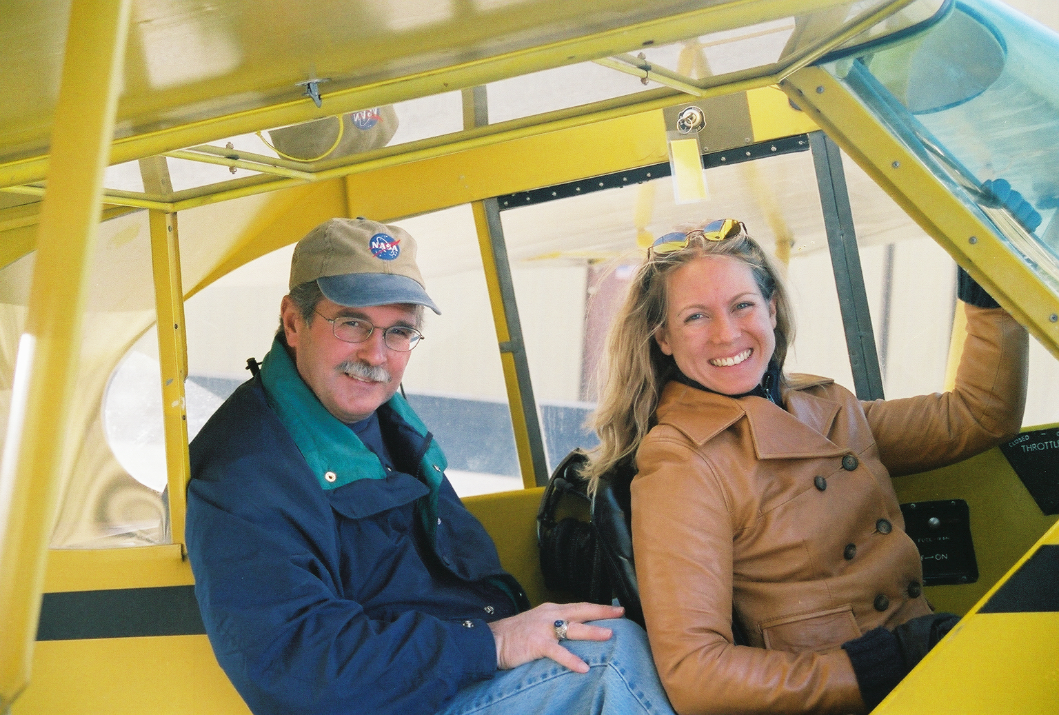 John and Heather Penney sitting in the cockpit of a yellow plane.
