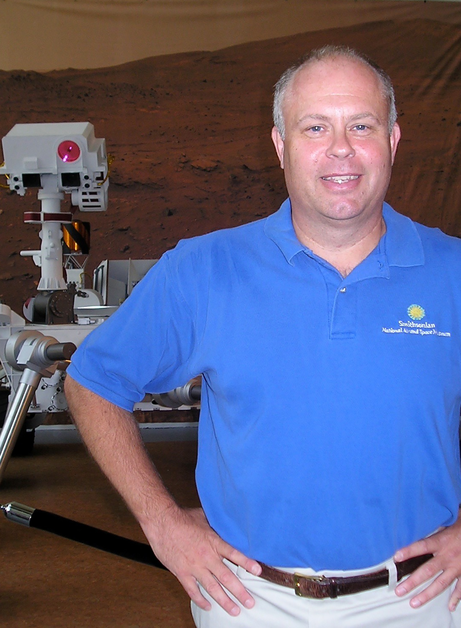 Dr. John Grant standing with a model of the Mars Curiosity Rover