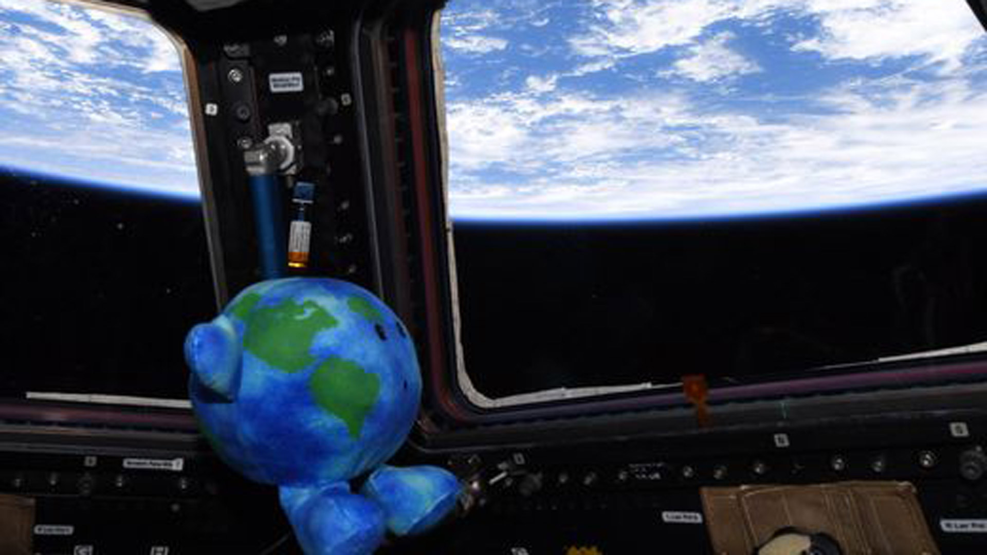 Celestial Buddies plush Earth toy is floating in the international space station. It is shaped and colored like a small Earth with a suprised expression. It is looking out a window towards Earth.