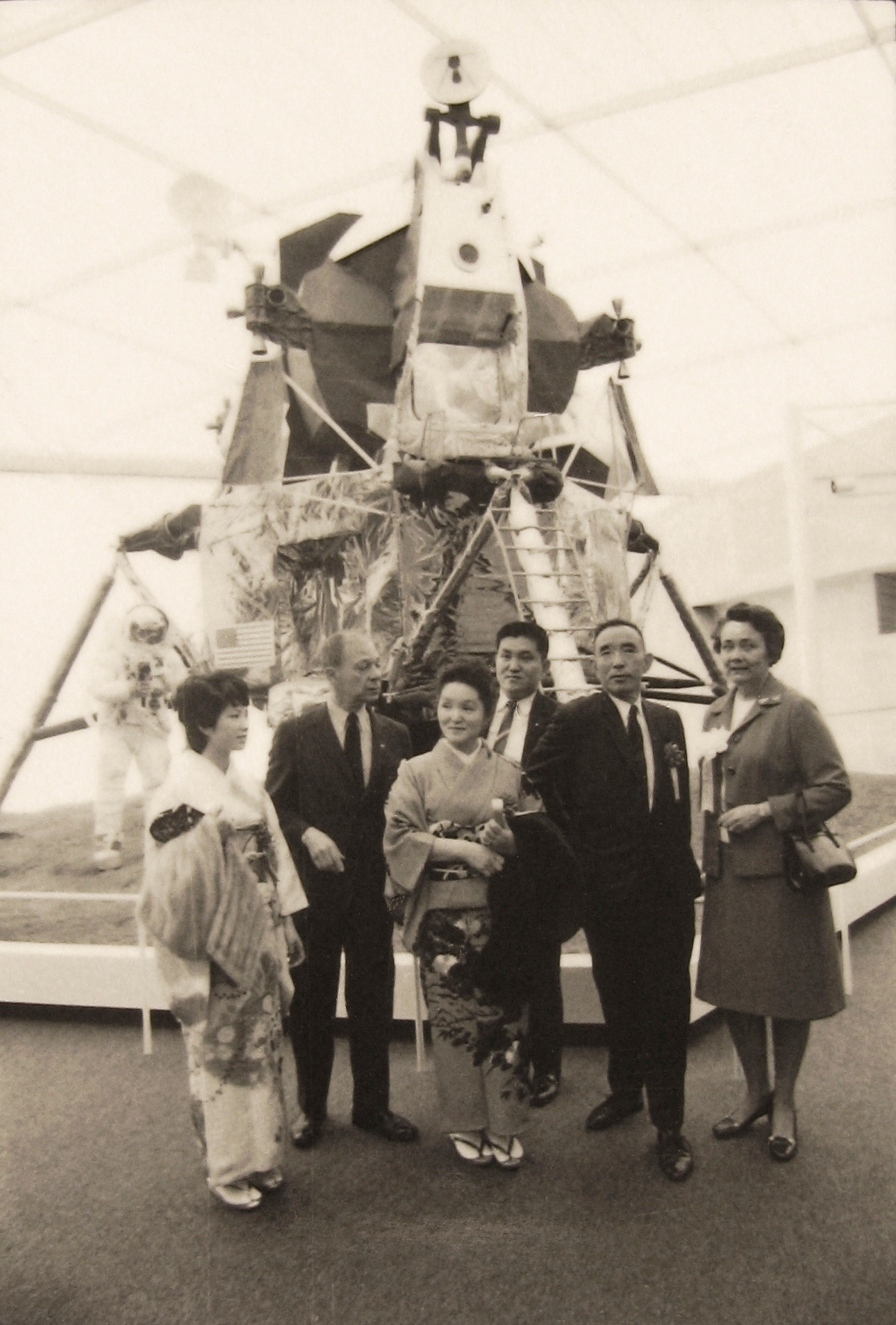 Black and white photo of dignitaries posing in front of the Lunar Module.