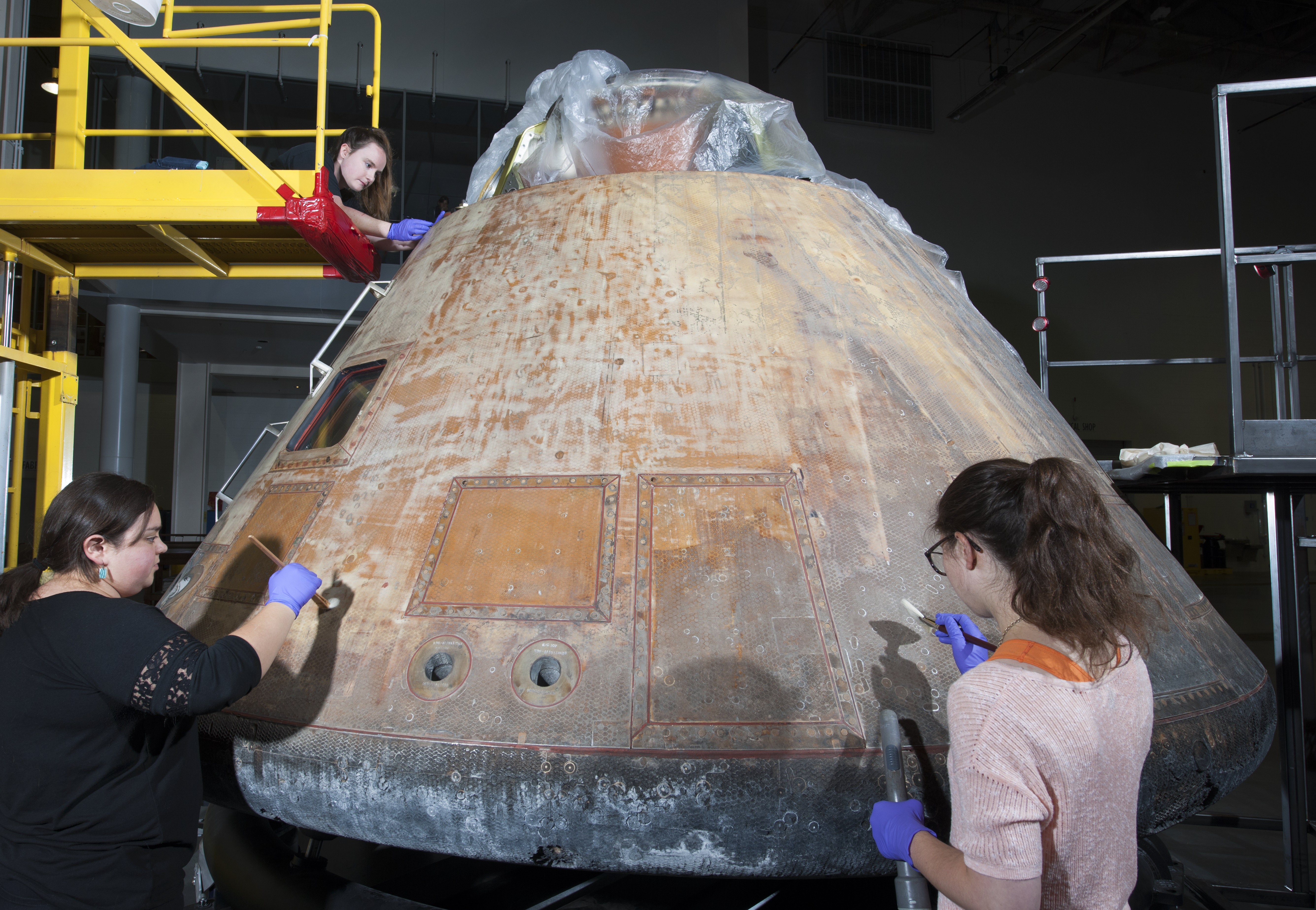 Conservators work on the Command Module Columbia