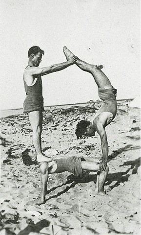 Doolittle and friends do tricks on the beach. Doolittle on the bottom holds up his other two friends who create a pyramid.
