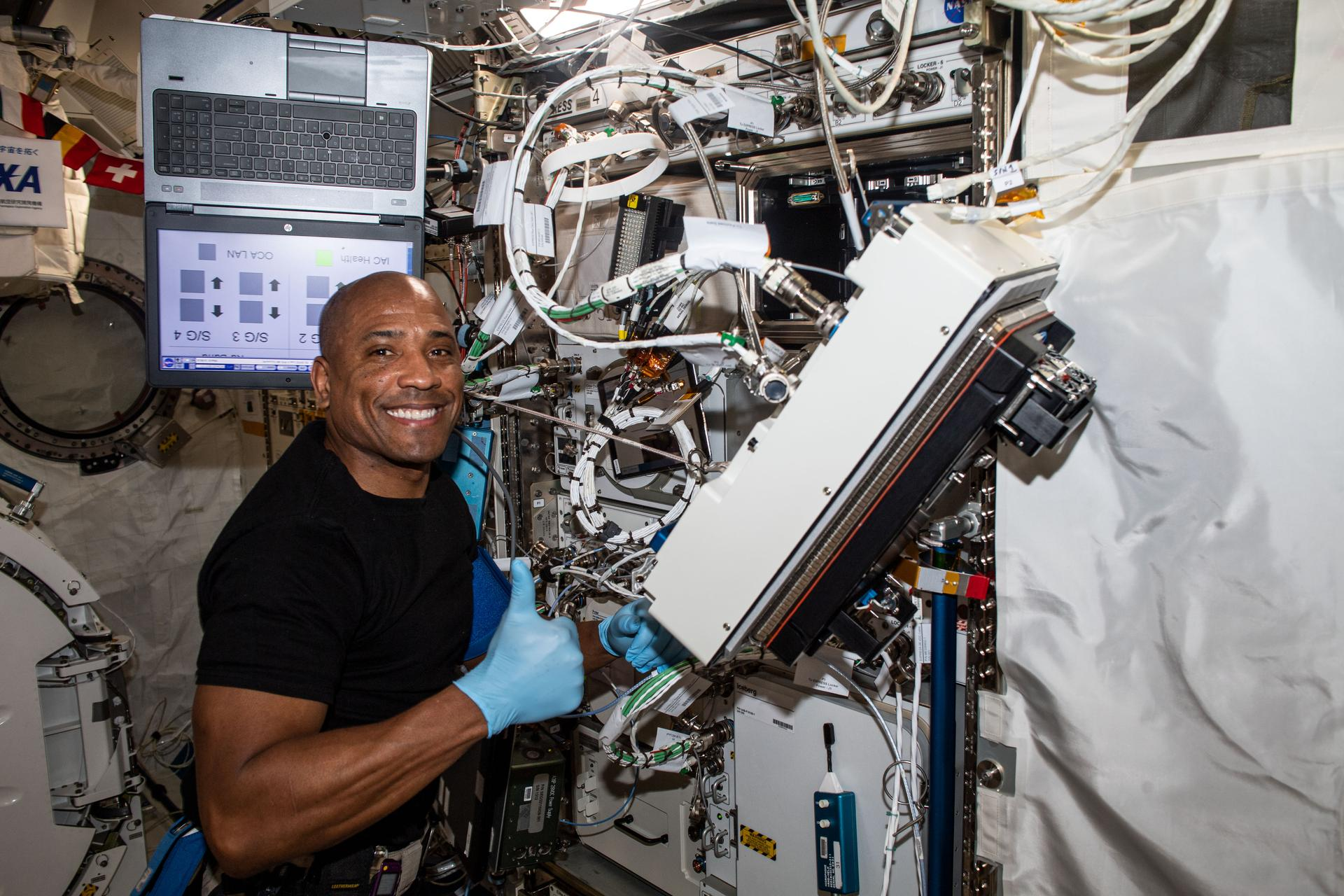 NASA astronaut and Expedition 64 Flight Engineer Victor Glover is pictured inside Japan's Kibo laboratory module installing research gear. He is looking at the camera and smiling. He is giving a thumbs up!