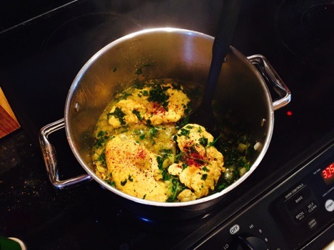 Chicken simmers in a pot on the stove.