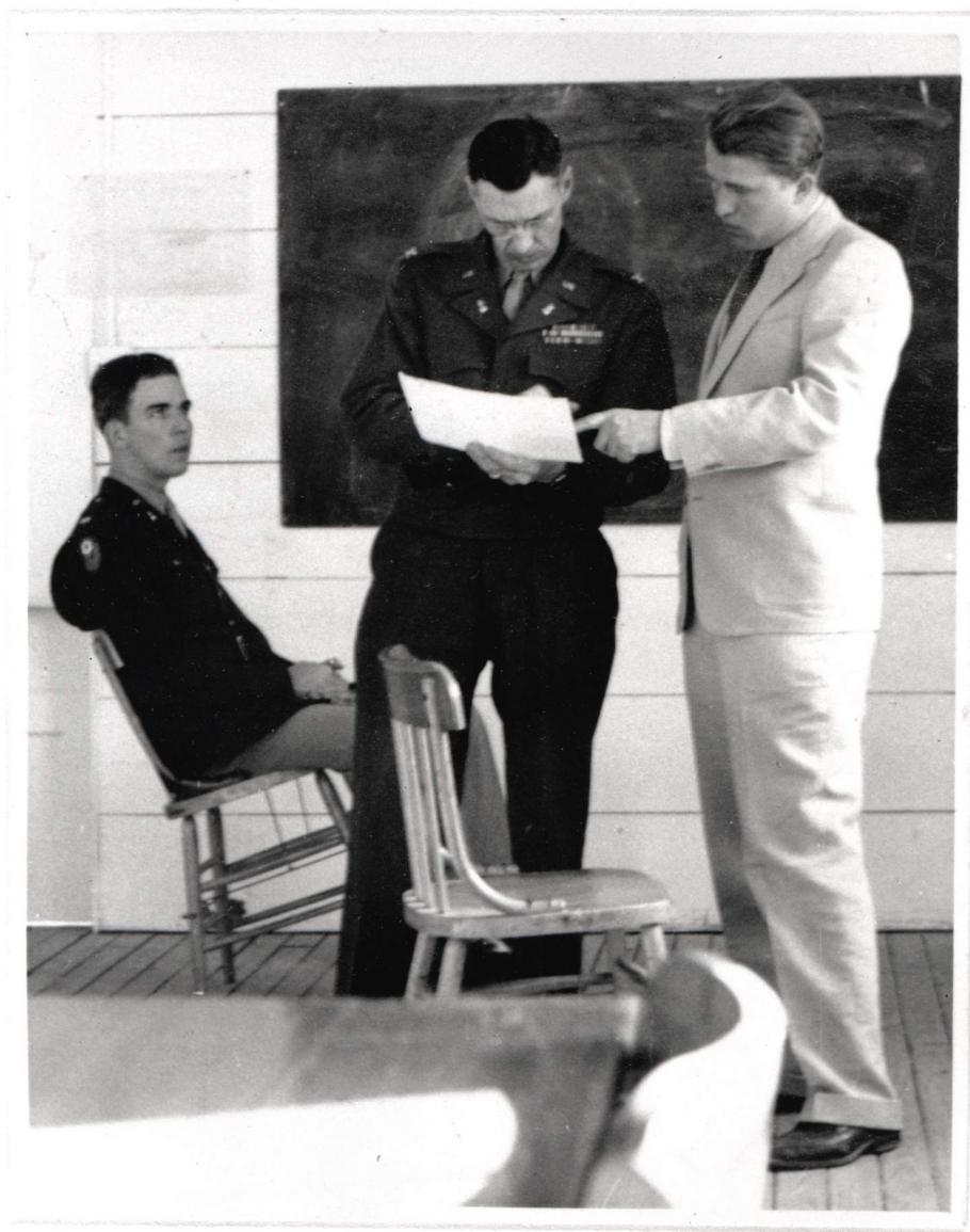 One man sits in a chair while two men stand up and look at a paper.