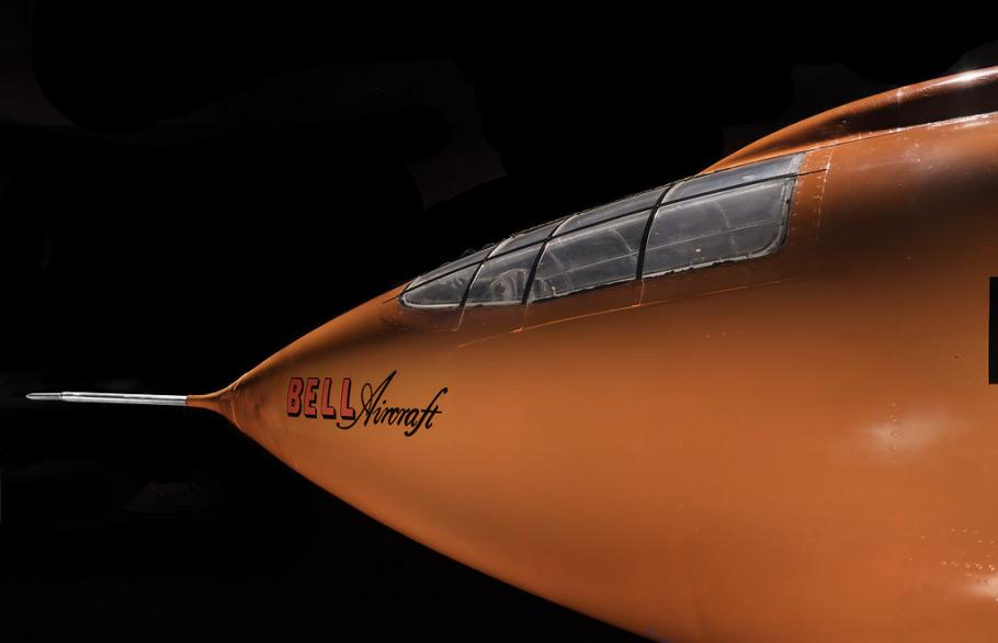 Side view of nose of an aircraft. The aircraft is painted orange.
