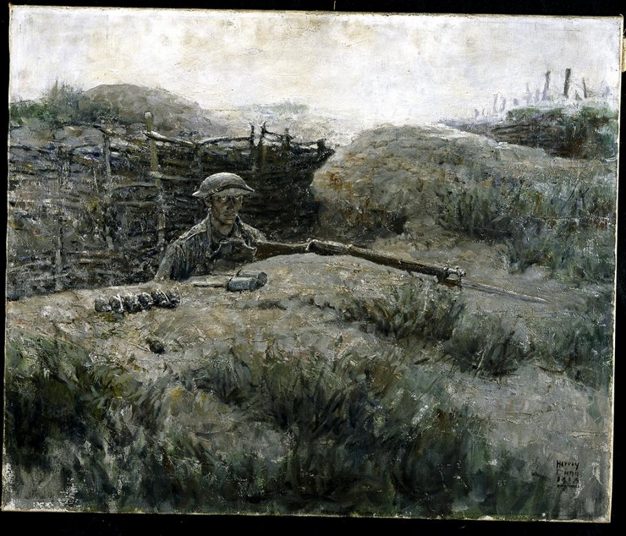 Man in military uniform looks out from a trench.