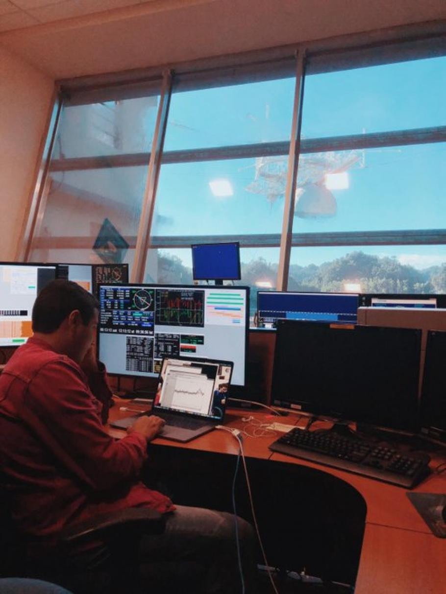 Young man sitting at a desk with computers. Telescope of the Arecibo Observatory can be seen out the window.