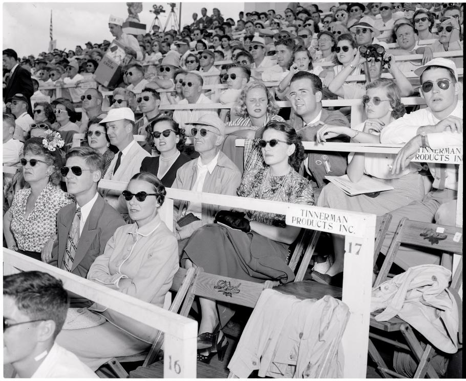 Spectators in a grandstand look to their left. Many wear sunglasses.