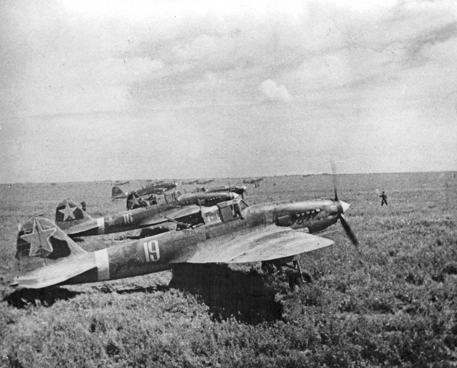 Historical photo of several aircraft on a grassy field.