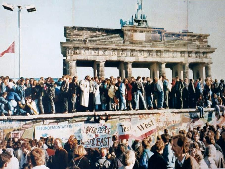 A crowd stands on the Berlin wall.