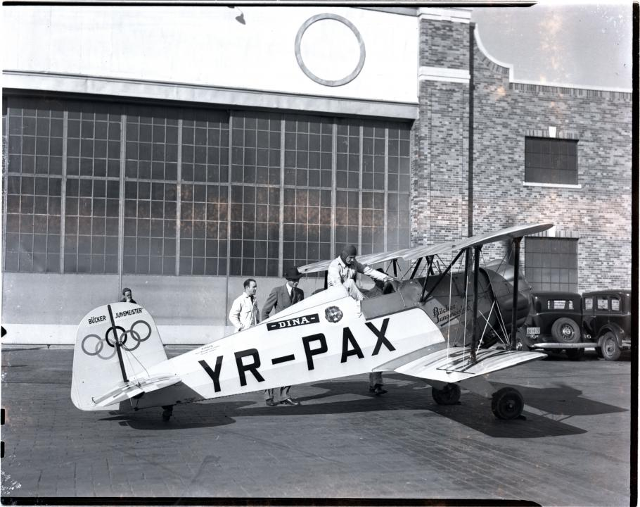 Profile of the Jungmeister with Olympic rings on the tail. Black and white photo.