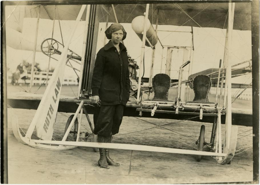 """Woman in Dark Buttondown Sweater and Laceup Boots stands in front of early aircraft, with """"Ruth Law"""" written on a part of the aircraft"""