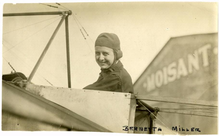 """Woman in flying headgear sits in the cockpit of an early airplane. Text in bottom right reads: """"Bernetta Miller."""""""