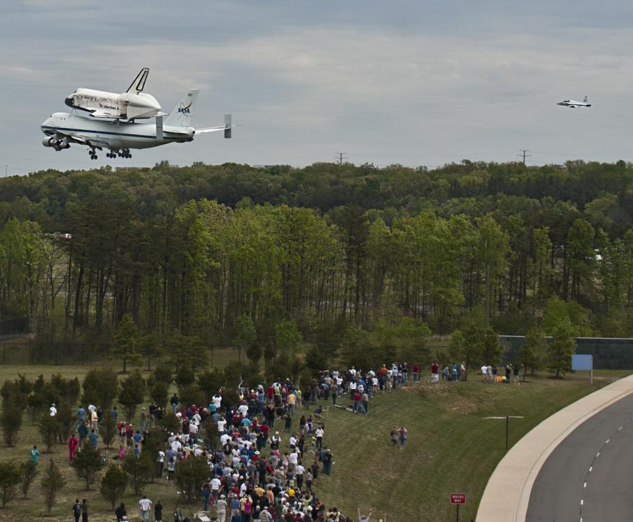 Space Shuttle Discovery flies low over crowd
