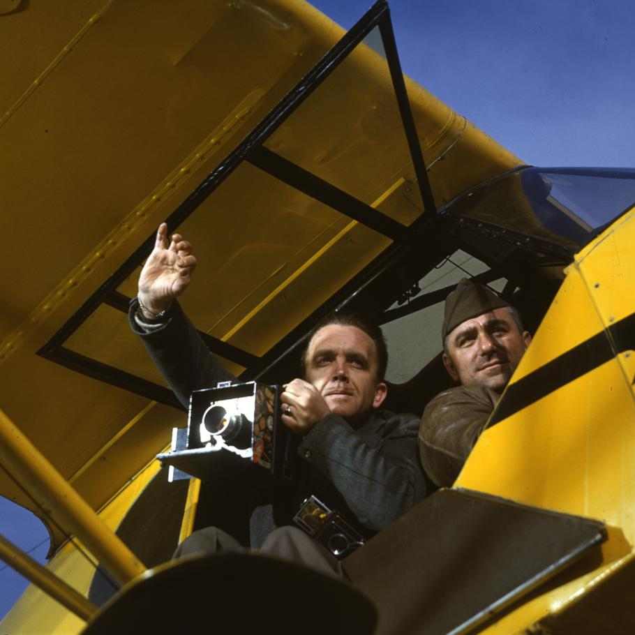 A photo taken from underneath an aircraft. One man leans out with a camera, the other is a pilot.