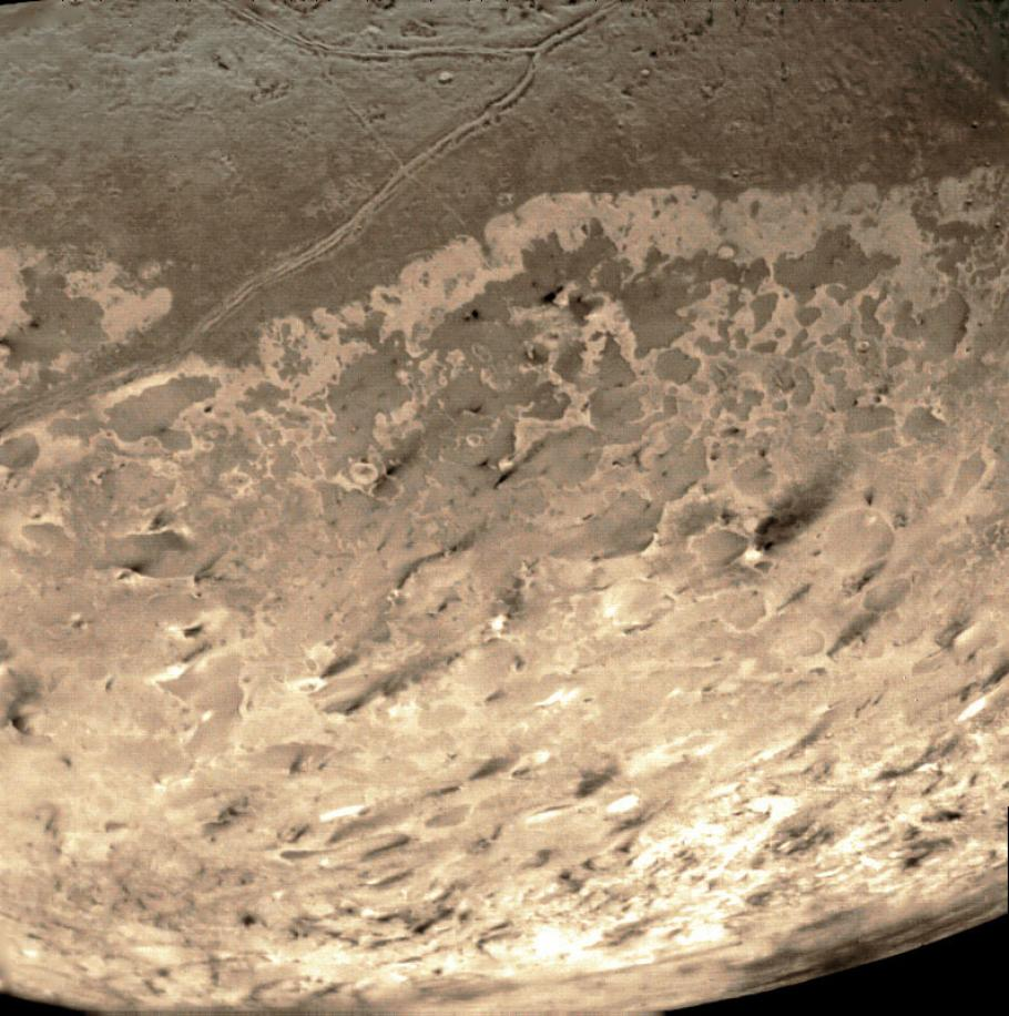 The dark streaks in this image are nitrogen geysers erupting at Triton's south pole.