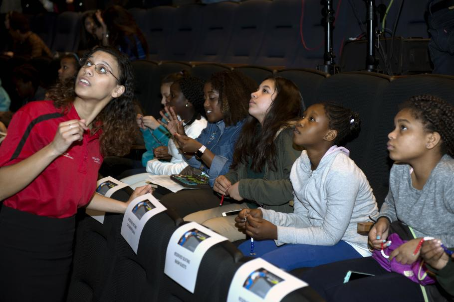 Students in a theater look up at a screen.