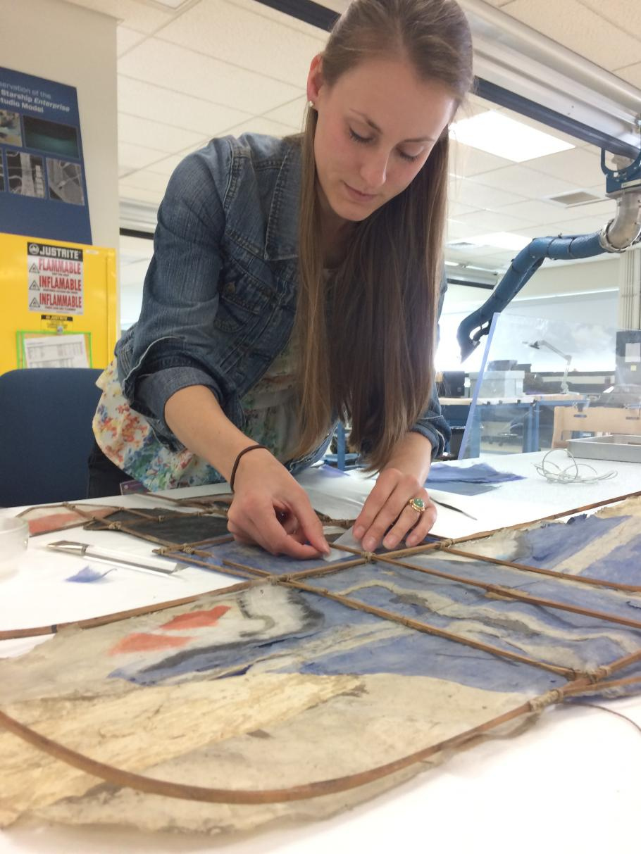 Intern Carolyn Burns working on a full conservation treatment of a Chinese paper kite from the National Air and Space Museum collection.