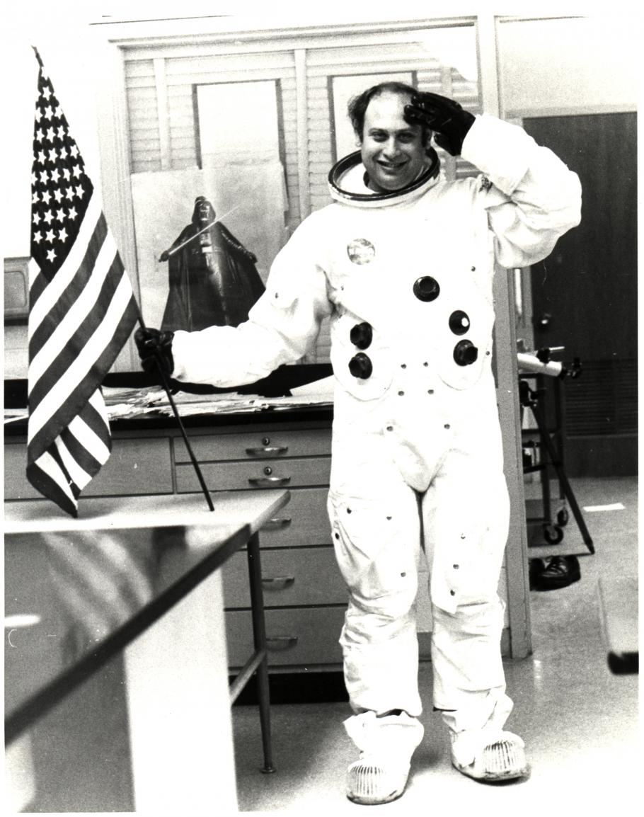 Man wearing space suit without a helmet salutes with his left hand while holding American flag in his right