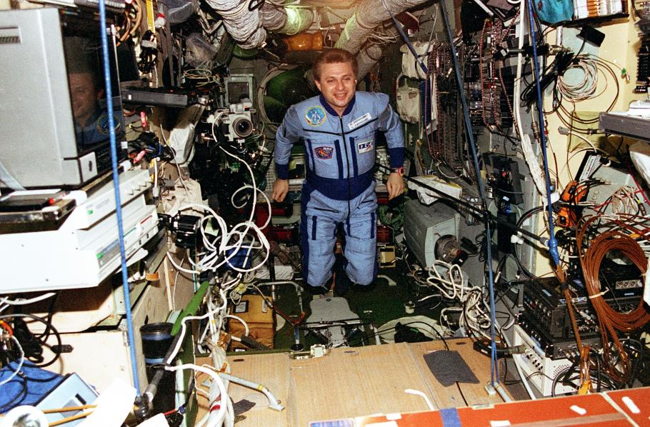 An astronaut floats inside the Mir Space Station, wires and tools float messily around him.