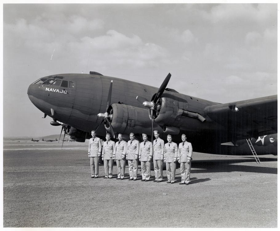 Group of pilots in front of commercial airliner during WWII