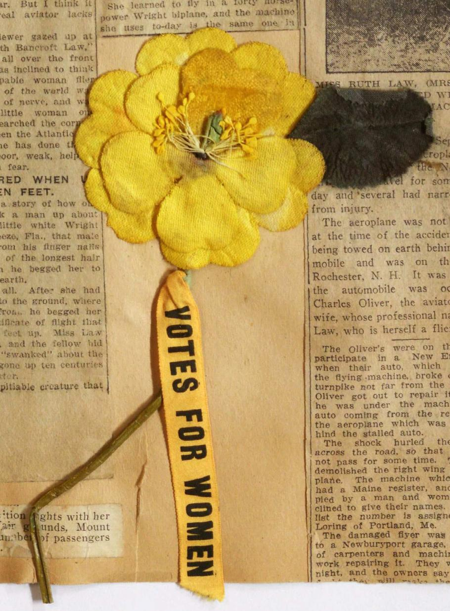 """Artificial flower, bright yellow double layer petals attached to light green wire stem; below stem yellow ribbon with black printed text """"VOTES FOR WOMEN"""""""