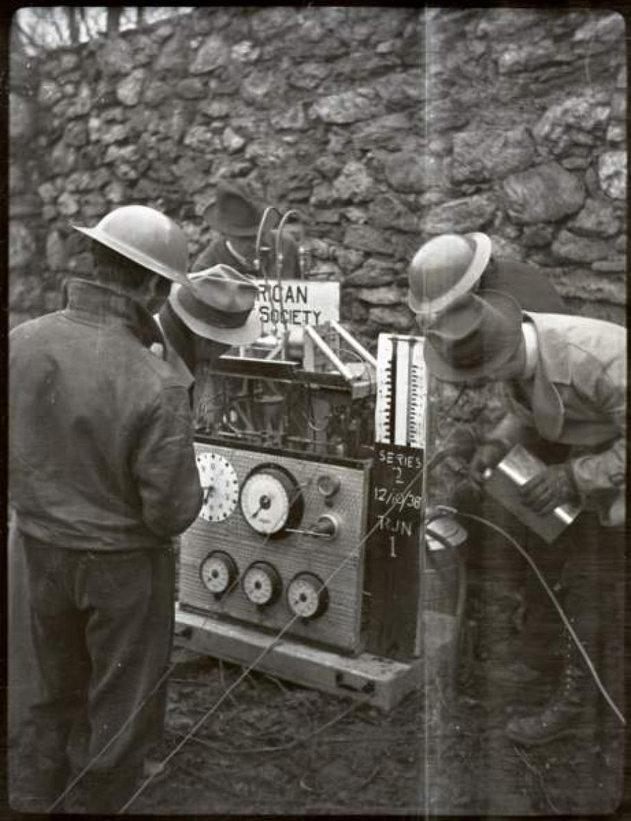 Black and white image of men in helmets working on a motor.