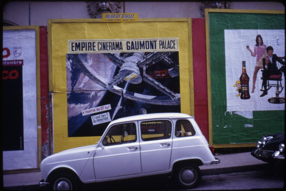 "A white vehicle is parked in front of a movie poster for the film ""2001: A Space Odyssey."""