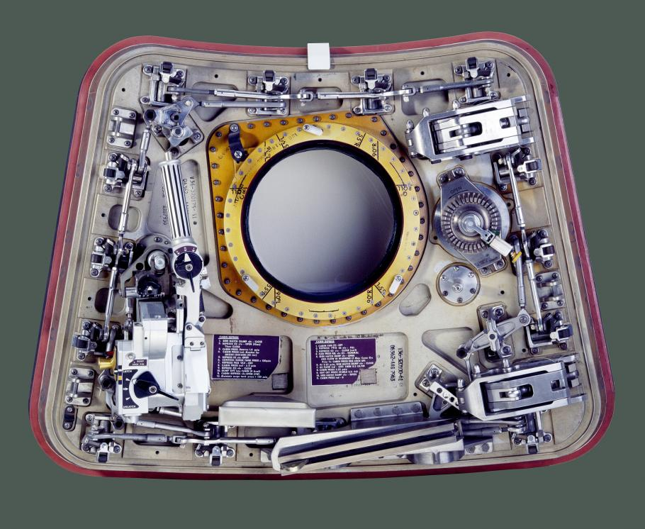 Image of a spacecraft hatch against a green background.