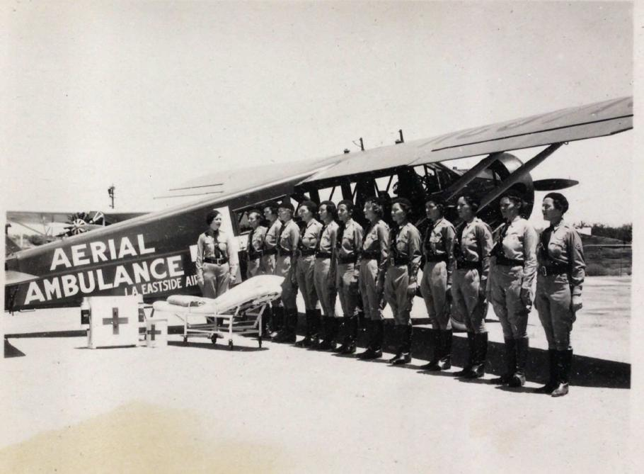 Fourteen women stand in a line in front of an aerial ambulance
