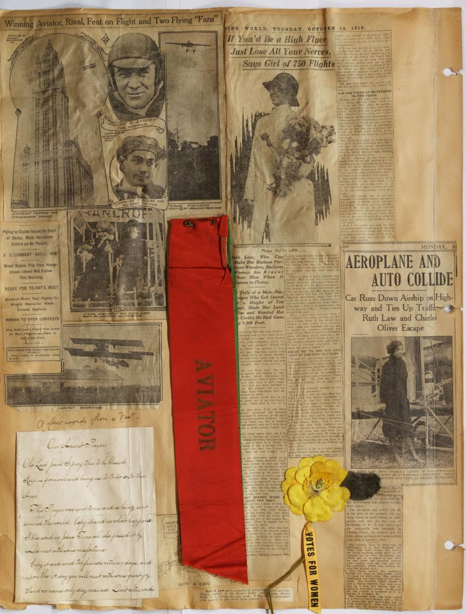 """Large Scrapbook page with newspaper clippings. Bottom right, white handwritten sheet; bottom middle; red rectangular ribbon """"Aviator""""; bottom right: yellow flower attached ribbon """"Votes for women"""""""