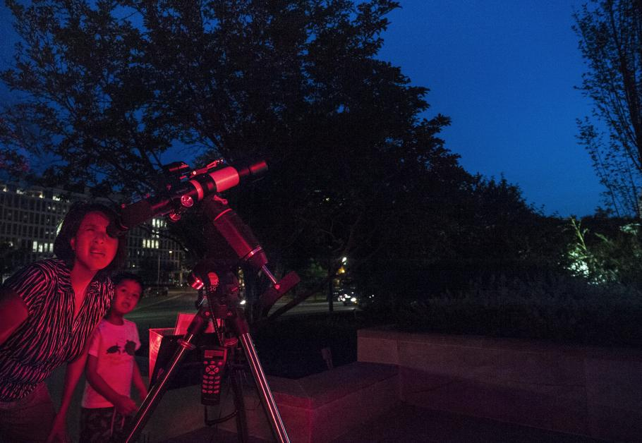 A mother and son use a telescope at night.