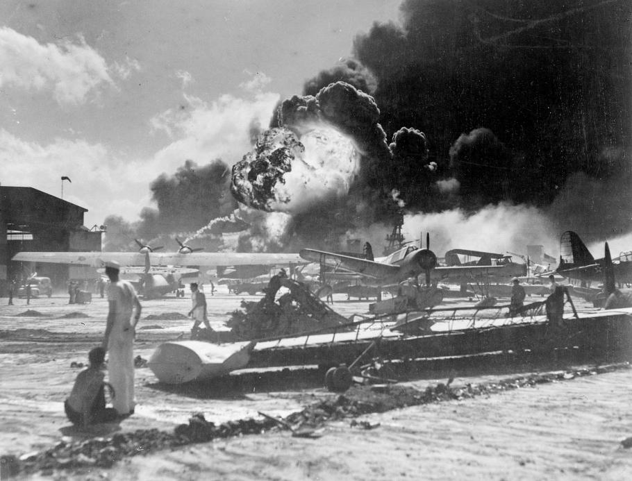 Sailors stand in the foreground. Damaged aircraft and explosions appear in background.