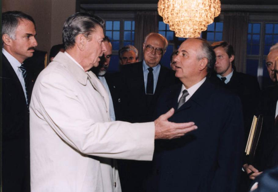 Reagan on left and Gorbachev negotiate amidst a crowd of onlookers.