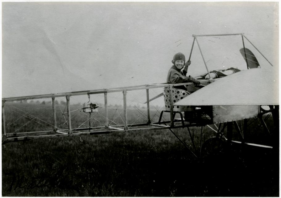 Rearview shot of an early airplane with Moisant in cockpit looking over her shoulder and smiling at the camera.