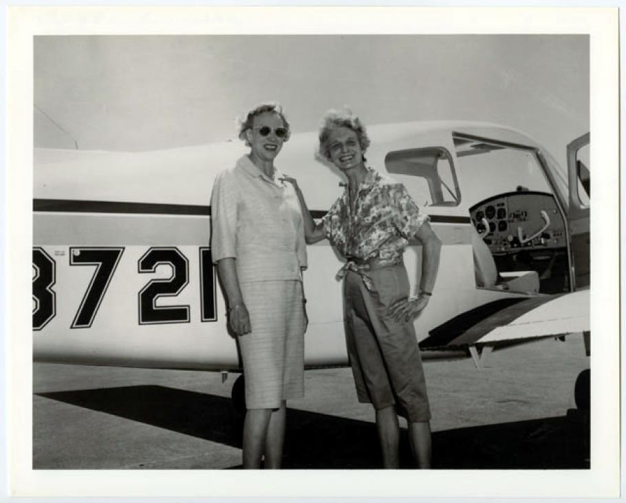 Black and white photo of Olive and Louise pose in front of airplane.