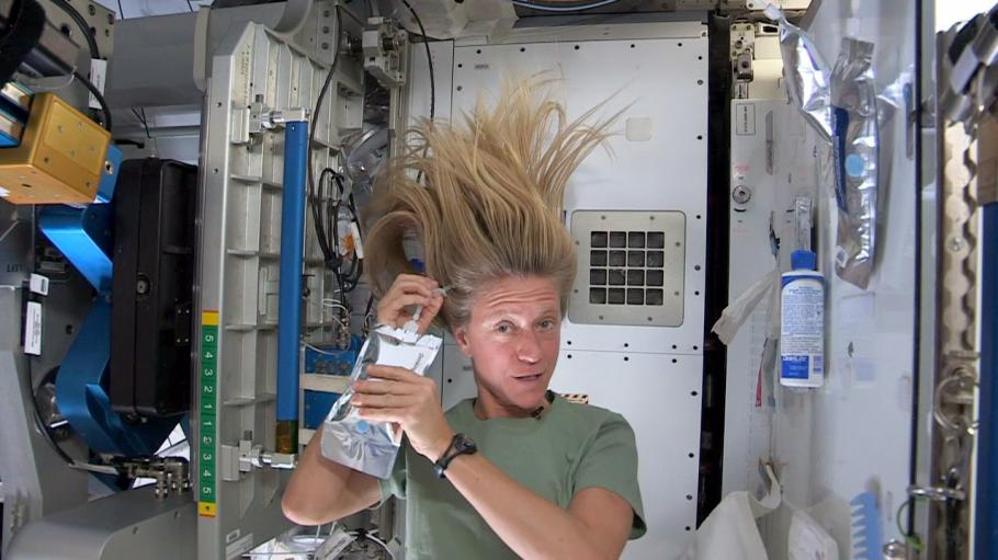 Astronaut demonstrates washing hair in space.