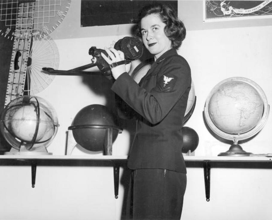 Woman in uniform stands in front of a series of globes and holds a link sextant.