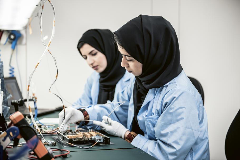 two women work on spacecraft