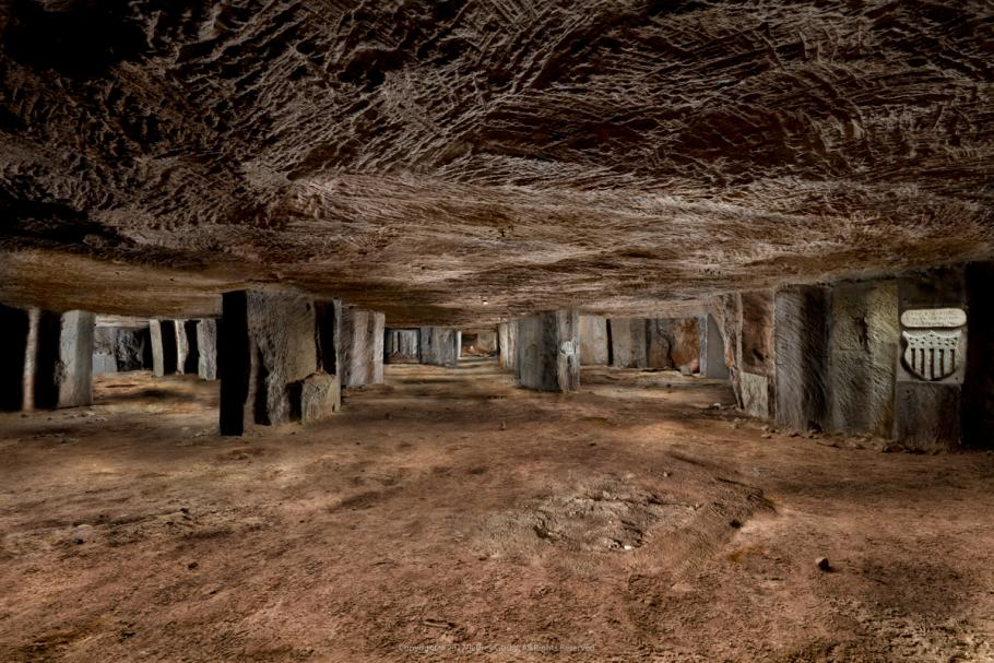 Expansive view underground with stone support columns and carvings visible.