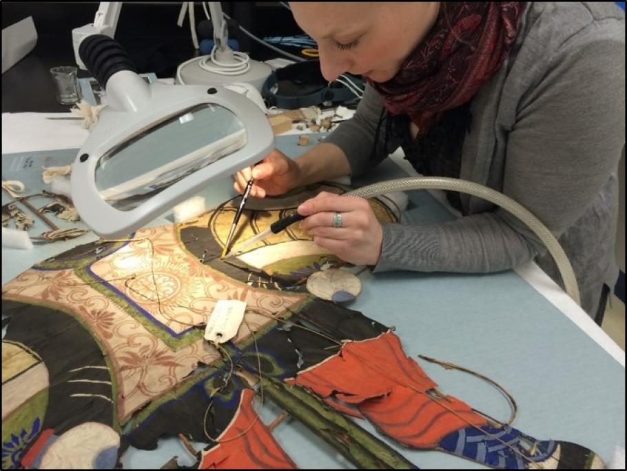 Conservator uses a small tube-like vacuum to clean a kite.