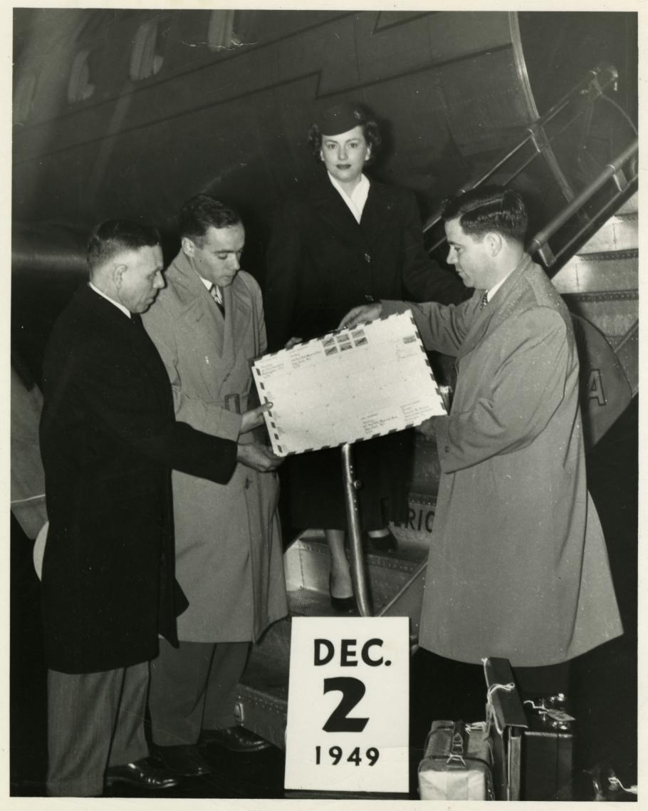 Three men and a woman in front of a Pan Am airplane