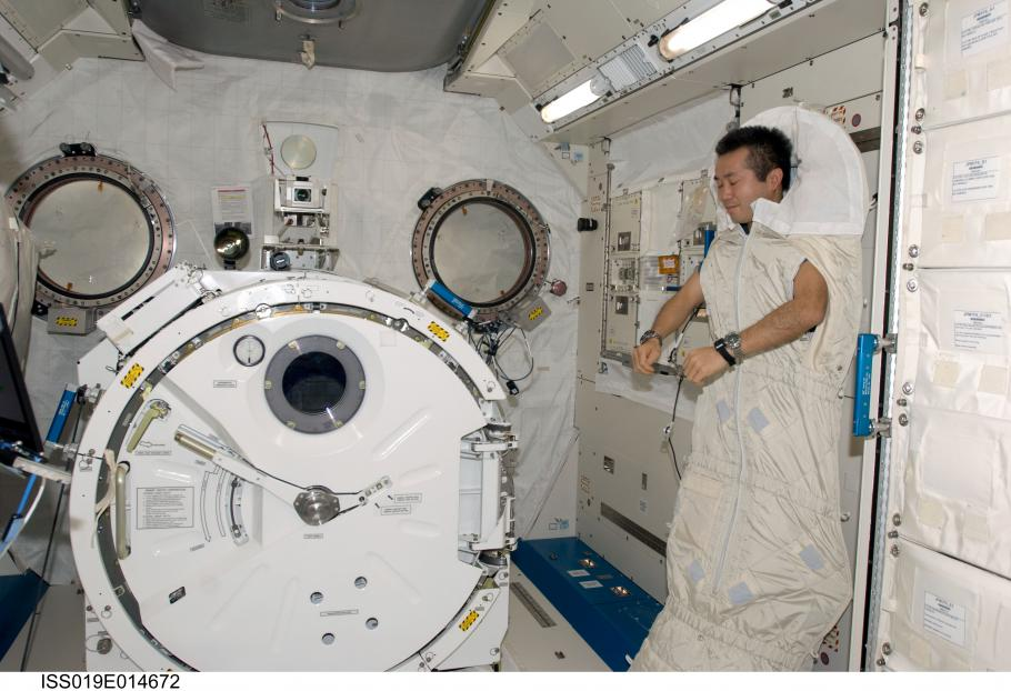 Astronaut is strapped into sleeping bed.